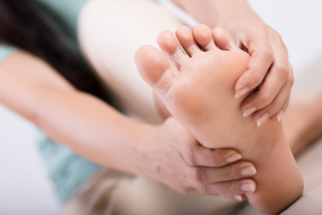 Mulher massageando seu pé doloroso, conceito de saúde.