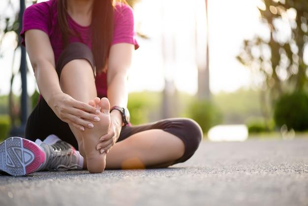 Mulher massageando seu pé doloroso durante o exercício. conceito de lesão do esporte.