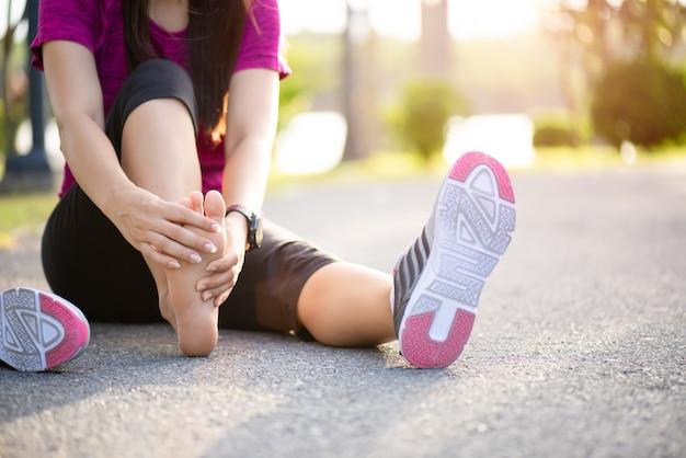 Mulher massageando seu pé doloroso durante o exercício. executando o conceito de lesão do esporte.
