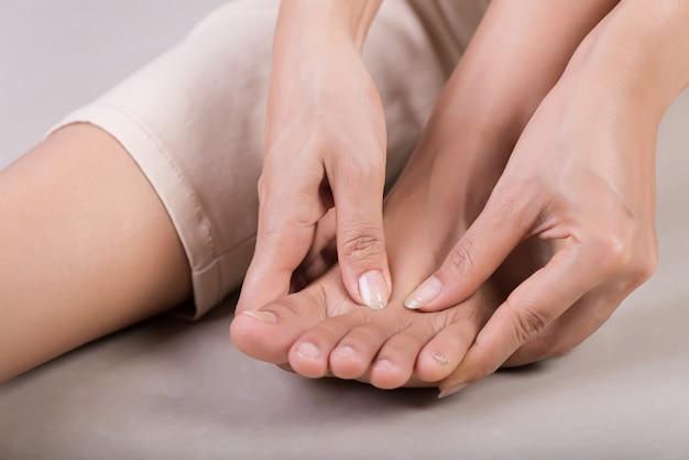 Mulher massageando seu pé doloroso.