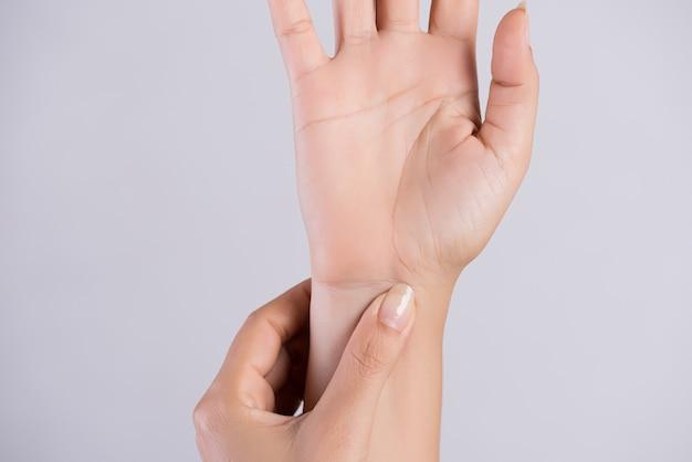 Mulher massageando seu pulso doloroso.