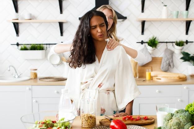 Mulher massageia ombros de mulher africana, ela sente dor