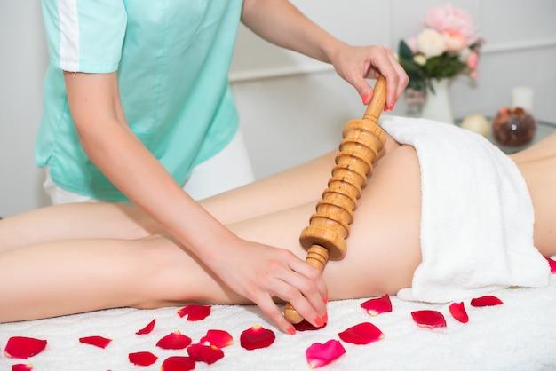 Mulher massagista fazendo massagem anticelulite, para uma jovem, um massageador de rolo de madeira. pernas cobertas com uma toalha branca.