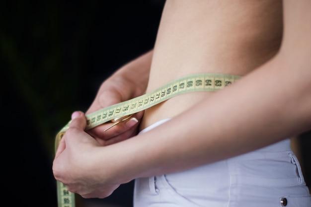 Mulher mede o volume da figura da cintura