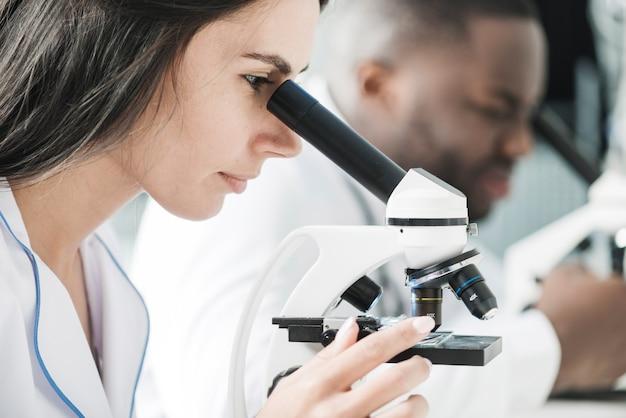 Mulher medic usando microscópio