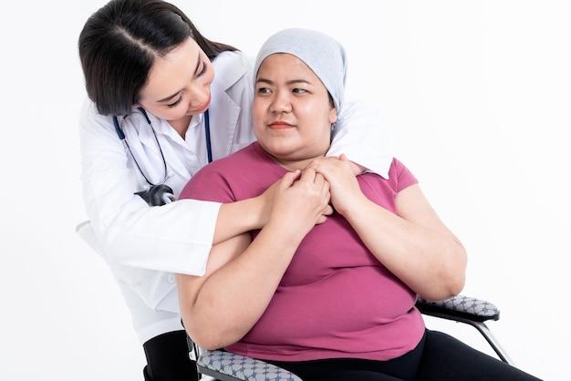 Mulher médica abraça a paciente que se sentou na cadeira de rodas para encorajar a combater a doença