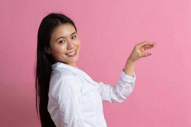 Mulher médica asiática em jaleco branco contra fundo rosa.