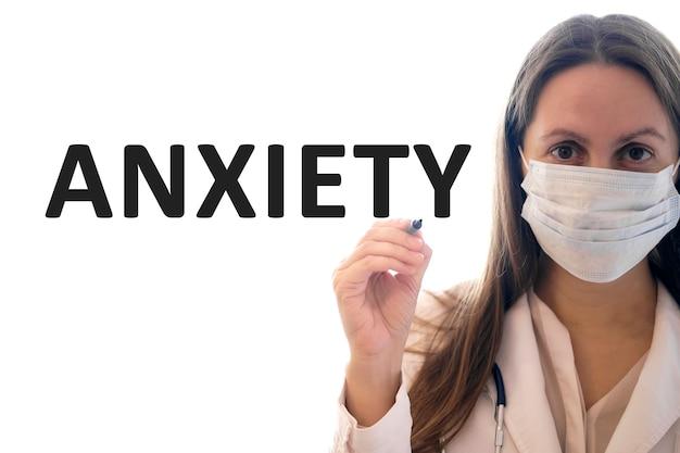 Mulher médica com uma máscara segura uma caneta e escreve um texto de ansiedade