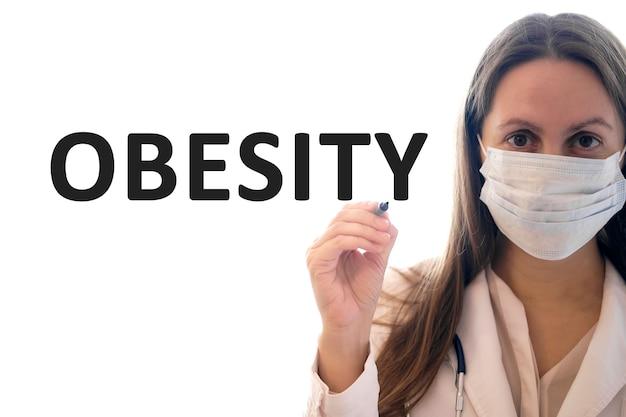 Mulher médica com uma máscara segura uma caneta e escreve um texto sobre obesidade