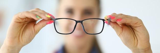 Mulher médica segurando óculos nas mãos, close up, conceito de exame e diagnóstico de visão