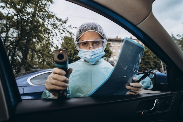 Mulher médica usa pistola de termômetro infravermelho para verificar a temperatura corporal
