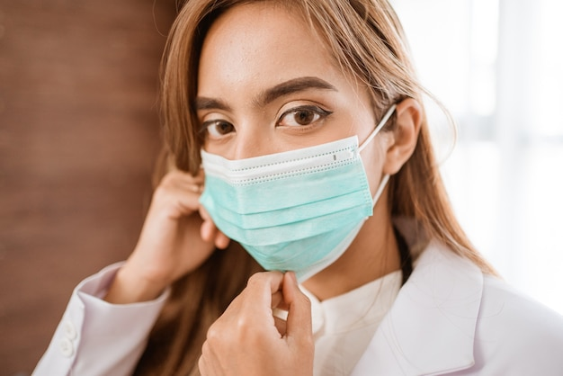 Mulher médica usando máscara médica em pé olhando para a câmera