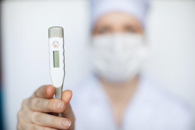 Mulher médica usando máscara médica mostrando um termômetro médico