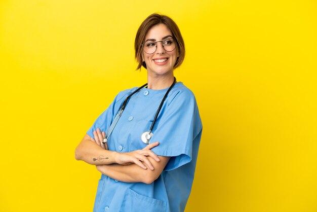 Mulher médico cirurgião isolada em fundo amarelo com os braços cruzados e feliz