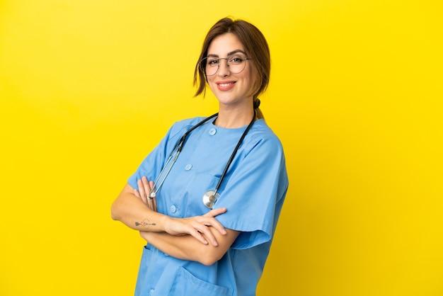 Mulher médico cirurgião isolada em fundo amarelo com os braços cruzados e olhando para a frente