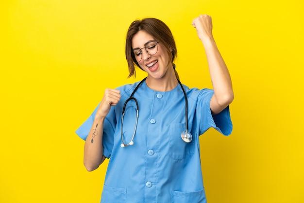 Mulher médico cirurgião isolada em fundo amarelo comemorando uma vitória