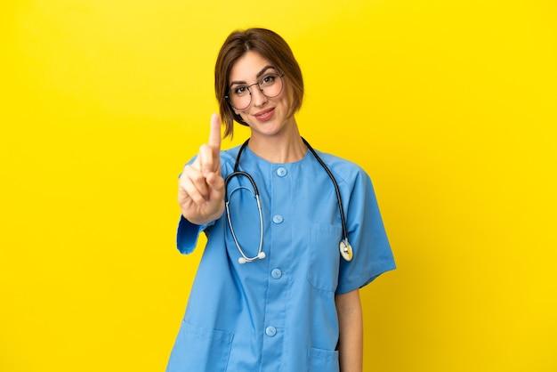 Mulher médico cirurgião isolada em fundo amarelo mostrando e levantando um dedo