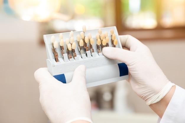 Mulher médico dentista segurando guia de cores de dente na clínica
