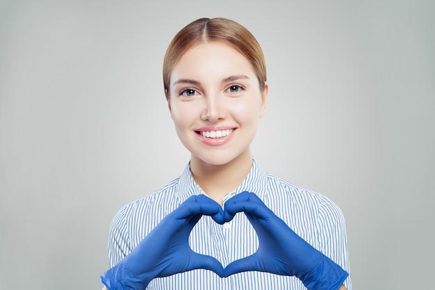 Mulher médico otimista em máscara protetora fazendo coração.