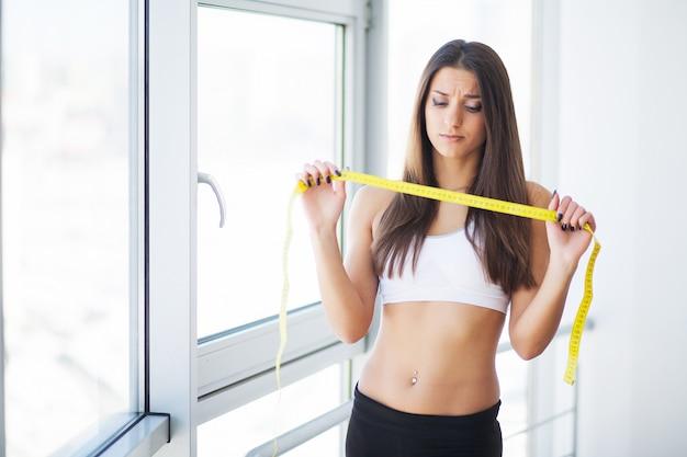 Mulher, medindo a cintura após o treino. mãos, medindo a cintura com uma fita. mulher magra e saudável