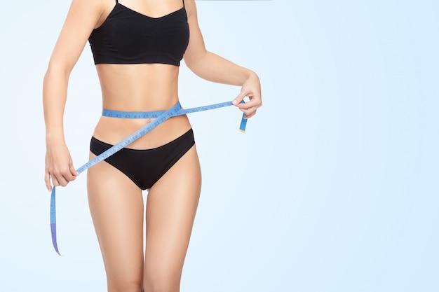Mulher, medindo a cintura com fita métrica azul