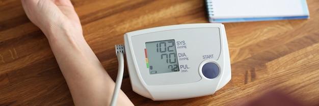 Mulher medindo a pressão arterial com o close up do tonômetro eletrônico. conceito de diagnóstico de hipertensão arterial