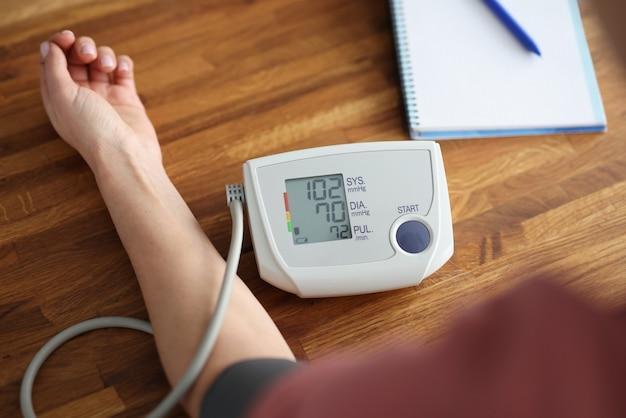 Mulher medindo a pressão arterial com o close up do tonômetro eletrônico. diagnóstico de artérias