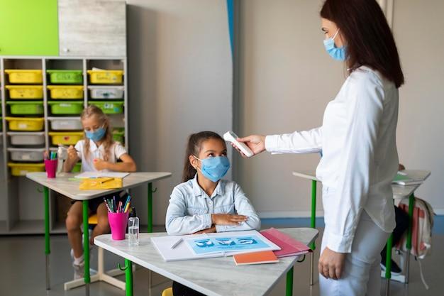 Mulher medindo a temperatura das crianças na sala de aula