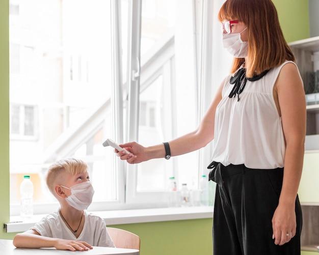Mulher medindo a temperatura de um menino na aula