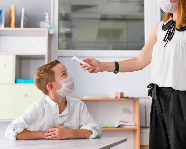 Mulher medindo a temperatura de uma criança na aula