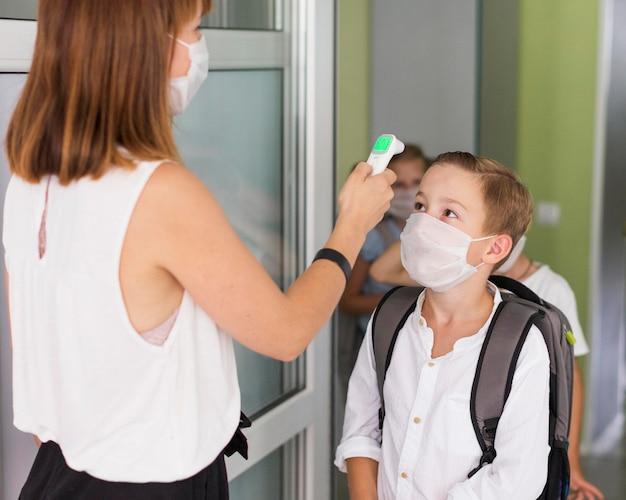 Mulher medindo a temperatura de uma criança