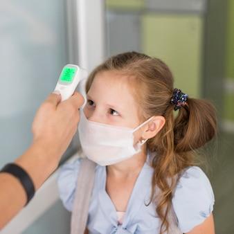 Mulher medindo a temperatura de uma menina