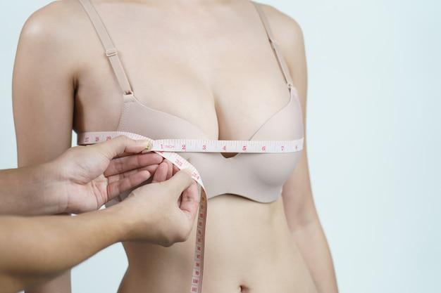 Mulher medindo o peito para cirurgia de implante mamário