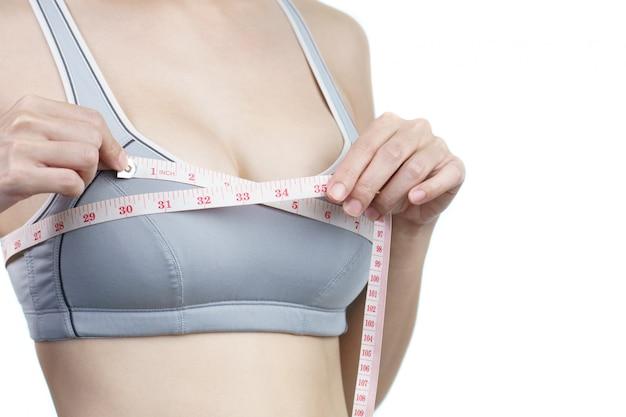 Mulher medindo o peito para cirurgia de implante mamário.