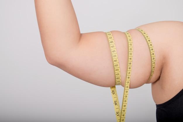 Mulher medindo os braços com fita métrica.