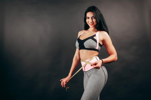 Mulher medindo seu corpo - conceito de fitness