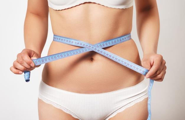 Mulher medindo seu corpo magro.