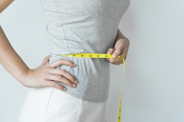 Mulher medir sua cintura.