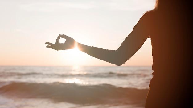 Mulher meditando ao pôr do sol na praia