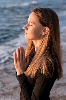 Mulher meditando de lado na praia