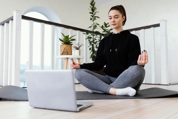 Mulher meditando dentro de casa