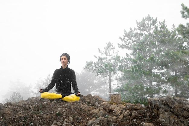 Mulher meditando e praticando ioga no topo da montanha