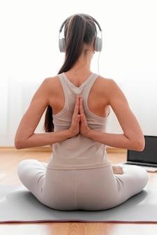 Mulher meditando em casa em casa com fones de ouvido