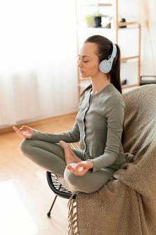 Mulher meditando em casa na cadeira