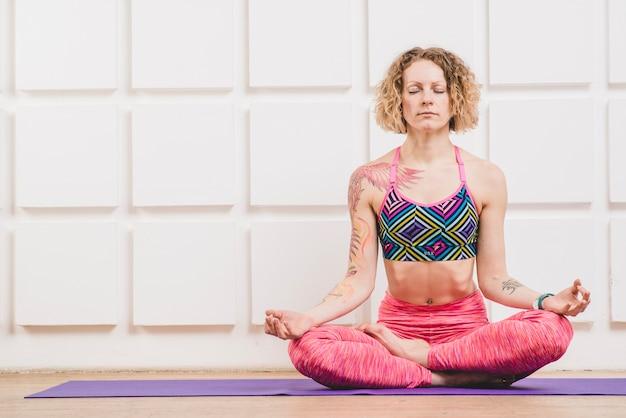 Mulher meditando em lótus asana em casa