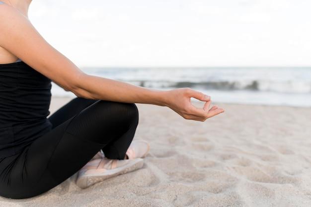 Mulher meditando em posição de lótus na areia