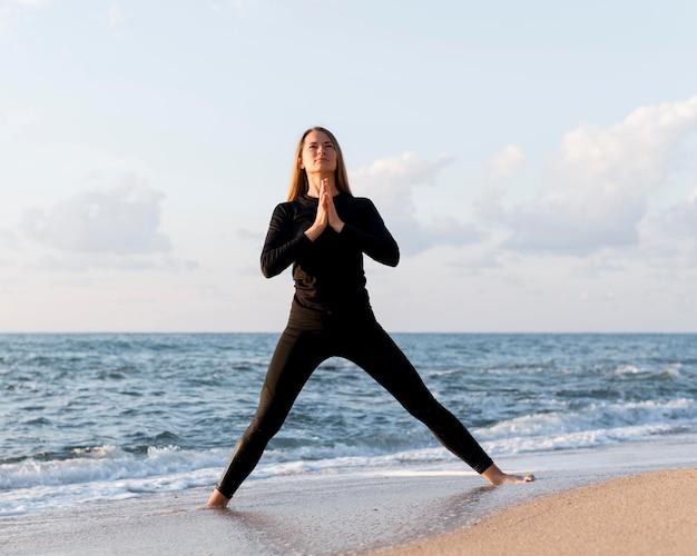 Mulher meditando na areia de frente