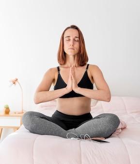 Mulher meditando na cama de frente