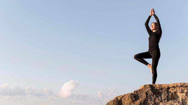 Mulher meditando na costa com espaço de cópia