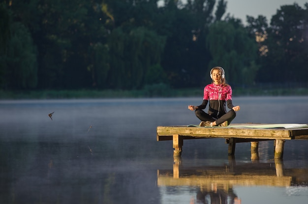 Mulher meditando na natureza no rio. ioga